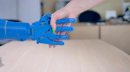 ingressou : A bionic hand being shaken by a human female one.