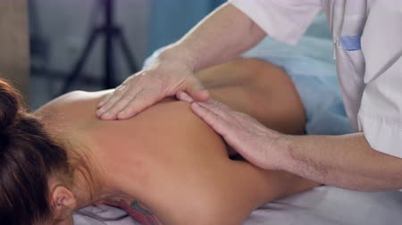 терапевт : Close up f the massage therapist massaging womans back