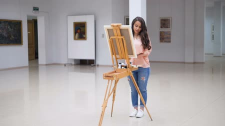 competence : Girl painting a picture in art gallery.