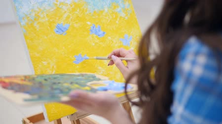 maquette : Woman painting blue flowers on yellow background. Stock Footage
