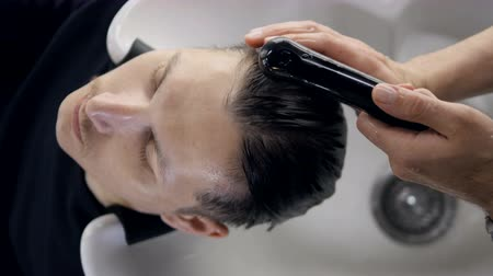 saç kremi : A hairdresser washes all product from male client head. Stok Video
