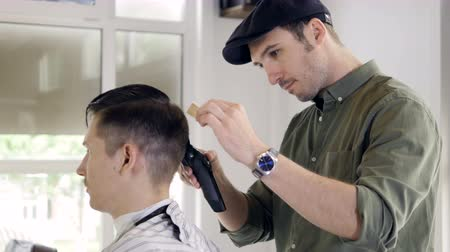 bigode : A man sits for a undercut styling.