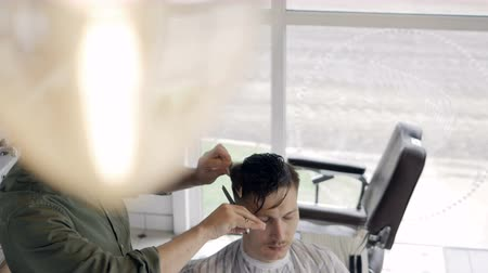 bigode : A barber chopping hair layers on a male client.