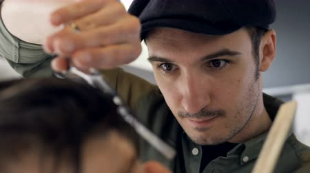 střih : Young barber makes the last touches to an undercut.