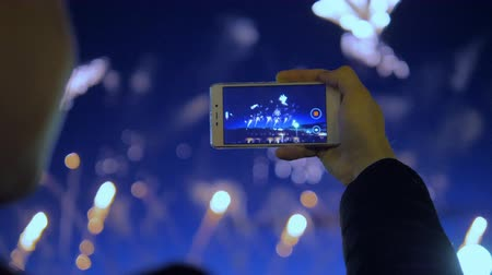 water show : The man is recording a video of fireworks with his phone.