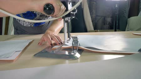 süet : A female worker cuts off excess fabric.
