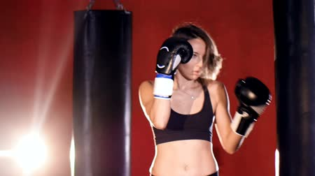 actively : Young woman boxing with punching bags. Slow motion.