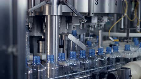 v řadě : Bottles transferred from a conveyor to a filling machine.