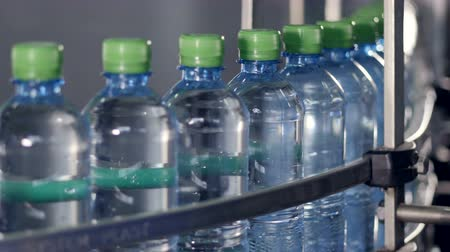 clear liquid : A conveyor belt full of filled and capped bottles.
