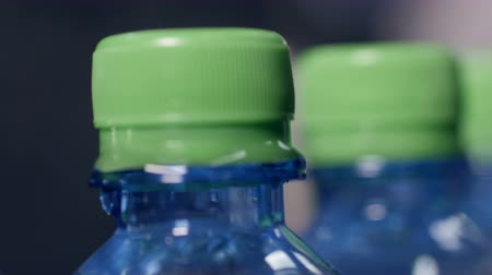 frasco pequeno : A closeup view of green caps on mineral water bottles.