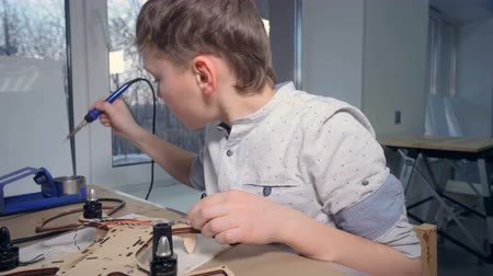 alicate : A young kid is soldering his modern flying gadget