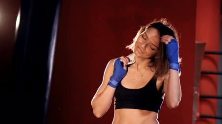 actively : Woman winner putting her gloves on her shoulder after mma fight. Stock Footage
