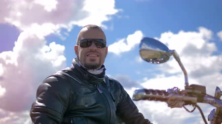 честолюбивый : Motorcyclist in sunglasses looking around and smiling.