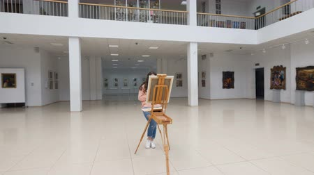 galeria : Girl standing in front of blank canvas.