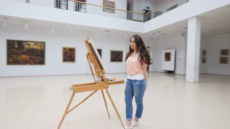 interpretation : Picture gallery, girl standing in front of blank canvas.