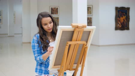 şaheser : Beautiful girl painting a picture on canvas. Stok Video