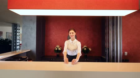 yönetici : Female receptionist smiling and giving key card at hotel lobby. Stok Video