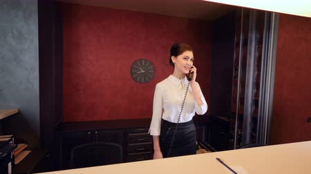 vendég : Beautiful female receptionist talking on the phone.