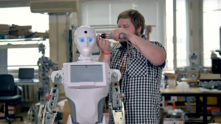 fixing : An operational robot has its head worked on.