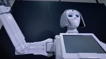 takip etmek : A low angle view of a robot hand wave greeting.