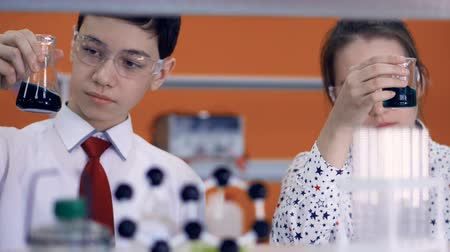 scrutiny : Young scientists mix and shake dark chemicals. Stock Footage