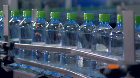 drinking water supply : Line of full bottles pushed through a conveyor.
