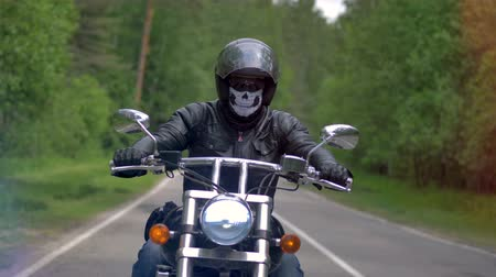 маска : A motorcyclist, biker on a lonely road drives wearing a skull mask. 4K.