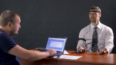 hozzákapcsol : A polygraph technician reads questions from a laptop. Stock mozgókép