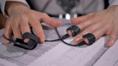 yalan : Male hands with lie detector sensors lie on large printouts with graphs. 4K.