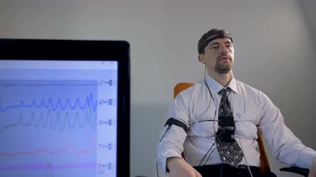 bizonyítani : A lie detector data on a screen when a man answers questions.