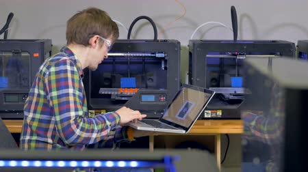 şematik : A young engineer debugs a 3d-printing problem. Stok Video