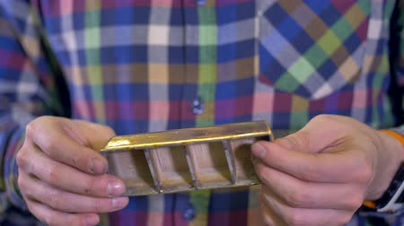 sahte : 3d-printed gold bar in male hands.