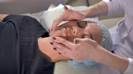 fingertips : Female face receives light finger touches after beauty procedures.