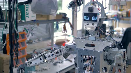 андроид : A robot in workshop with all inner parts visible.