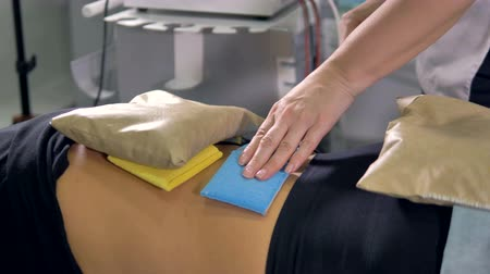 chronic : A doctor applies physiotherapy applicators on patients back. Stock Footage