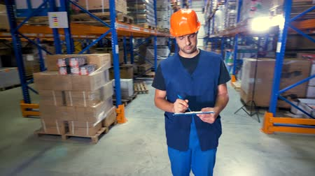 jelölőnégyzetet : A young serious warehouse inspector works at a storage facility.