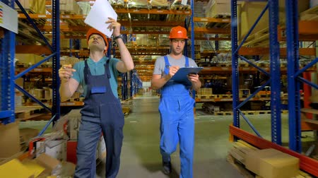хранилище : Two warehouse employees compare storage placement with their printed plans.