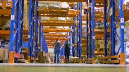 yarda : Two warehouse inspectors walk in a long corridor.
