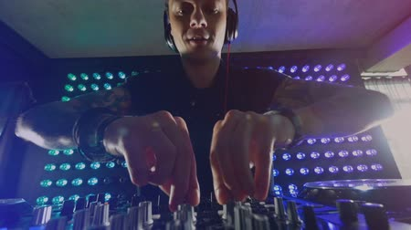 toggle : A DJ experiments with different knobs at his mixer.