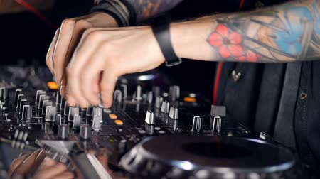 toggle : A side view on a DJs hands creating music.