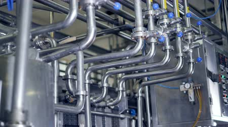 distillation : A low view on a piping system with blue valves.