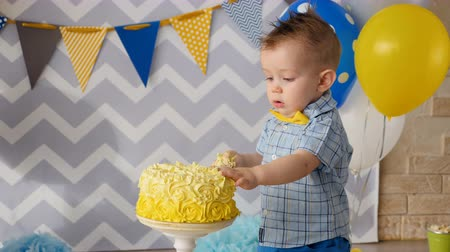 smashing : A small boy sticks his fingers inside a cake.