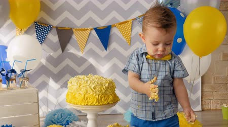 smashing : A toddler boy with cake spots on his face. Stock Footage