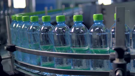 deslizamento : A conveyor line moves full water plastic bottles heavily.