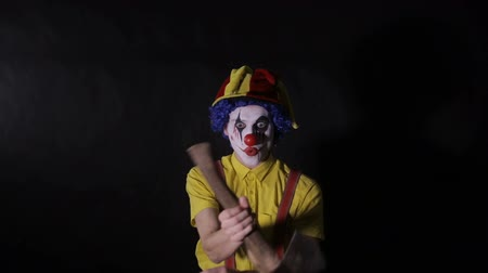 scary clown : A crazy clown plays with an axe.