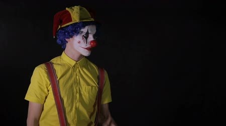 scary clown : A clown juggles a wooden axe with one hand.