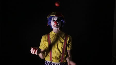 scary clown : A clown juggles red apples and shows his teeth.