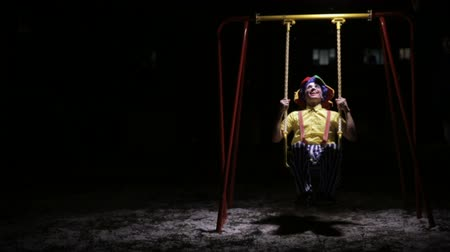 hátborzongató : A clown rides low children swings in the dark.