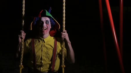 запятнанный : A clown with bloody makeup on swings.