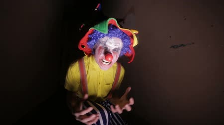scary clown : A scary clown in a dark alley makes faces.